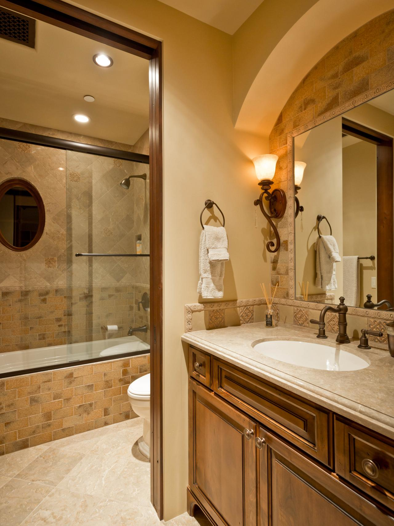 Mediterranean Bathroom with Tilework and Arch Over Vanity
